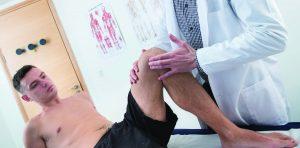 Chiropractor teaching footballer